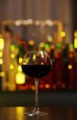Glass of red wine in bar on blurred background — Stock Photo