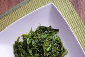 Seaweed salad in plate on bamboo mat and wooden table background — Stock Photo