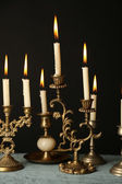 Retro candlesticks with candles on wooden table, on black background — Stok fotoğraf
