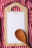 Cutting board with menu sheet of paper on squared fabric background — 图库照片