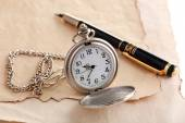 Silver pocket clock on old paper background — Stock Photo
