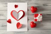Beautiful hand made post card  with paper hearts on color wooden background — Φωτογραφία Αρχείου