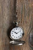 Silver pocket clock on wooden background — Stock Photo