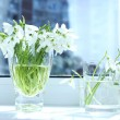 Beautiful bouquets of snowdrops in vases on windowsill — Stock Photo #62570017