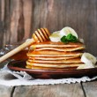 Stack of pancakes with mint, honey and slices of banana on rustic wooden background — Stock Photo #62571157