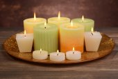 Beautiful candles on table on brown background — Stock Photo
