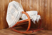 Rocking chair covered with plaid on wooden wall background — Stockfoto