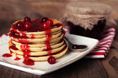 Stack of delicious pancakes with cranberries and jam on plate and napkin on wooden background — Stock Photo