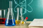 Desk in chemistry class with test tubes on green blackboard background — Stock Photo