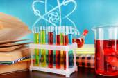 Glassware with chemical agent on desk, on green blackboard background — Stock Photo