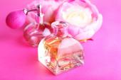 Bottle of perfume with peony on pink background — Stock Photo