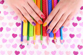 Multicolor female manicure with markers and pencils on bright background — ストック写真