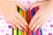 Multicolor female manicure with markers and pencils on bright background — Photo