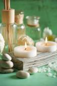 Candles, bottles sea salt and spa stones on wooden background — Foto de Stock