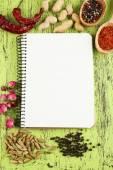 Gewürze mit Rezeptbuch auf farbigem Hintergrund Holztisch — Stockfoto