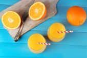 Glass of orange juice with straws and slices on cutting board with knife on color wooden background — Stock Photo