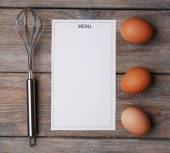 Menu sheet of paper with egg whisk and eggs on rustic wooden surface background — Stock Photo