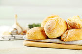 Fresh homemade bread buns from yeast dough on wooden tray, on color wooden background — Stok fotoğraf