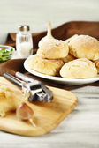 Fresh homemade bread buns from yeast dough on wooden cutting board, on color wooden background — Stok fotoğraf