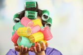Girl in hair curlers on bright background — Stock Photo