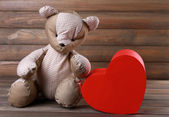 Teddy Bear with red heart on wooden background — Stock fotografie