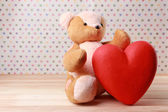 Teddy Bear with red heart on festive background — Stock Photo