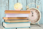 Books with clock on wooden background — Stock Photo