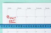 Diet concept - measure tape on calendar, close up — Стоковое фото