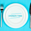 Plate with text Dinner Time, fork and knife on tablecloth background — Stock Photo #62771355