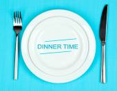 Plate with text Dinner Time, fork and knife on tablecloth background — Stock Photo
