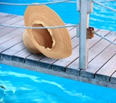 Summer hat on wooden bridge — Stock Photo
