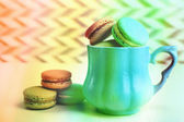 Assortment of gentle colorful macaroons in mug on color and textured background — Stock Photo