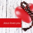 Heart with rosary beads on wooden background and text Jesus loves you — Stock Photo #62833801