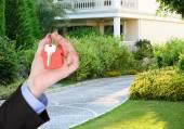Ключ в руке на фоне дома, понятии недвижимости — Стоковое фото