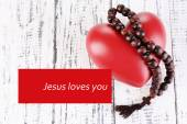 Heart with rosary beads on wooden background and text Jesus loves you — Stock Photo