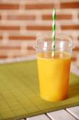 Orange juice in fast food closed cup with tube on wooden table and brick wall background — Stock Photo