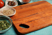 Different spices and herbs with cutting board on color wooden table background — Stock fotografie