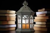 Books and decorative lantern on table and dark background — Stock Photo