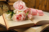 Books with flowers and clock on wooden background — Stock Photo