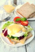 Toast with egg Benedict and tomato on plate on wooden table — Stock Photo