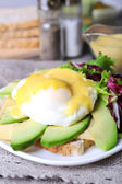 Toast with egg Benedict and avocado on plate on table close up — Stock Photo