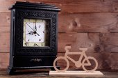 Retro clock with decorative bicycle on table on wooden background — Stock Photo