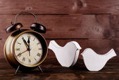 Retro clock with decorative birds on table on wooden background — Stock Photo