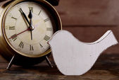 Retro clock with decorative bird on table on wooden background — Stock Photo