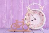 Beautiful vintage alarm clock with decorative bicycle on table on wooden background — Stock Photo