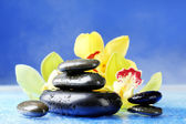 Spa stones with steam and beautiful blooming orchid on blue background — Foto de Stock