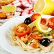 Tasty pasta with shrimps, black olives and tomato sauce on plate on wooden background — Stock Photo #62948247