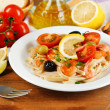 Tasty pasta with shrimps, mussels, black olives and tomato sauce on plate on wooden background — Stock Photo #62948269