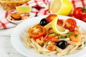 Tasty pasta with shrimps, black olives and tomato sauce on plate on wooden background — Stock Photo