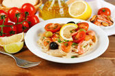 Tasty pasta with shrimps, mussels, black olives and tomato sauce on plate on wooden background — Stock Photo